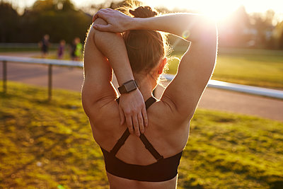 Young Woman Wearing Activity Tracker Stretches Before Run - p1407m1508967 by Monkey_Images