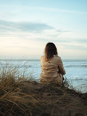 Woman in trenchcoat sitting on the beach, rear view - p1522m2273343 by Almag