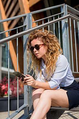 Businesswoman sitting on stairs using cell phone - p300m1166284 by Mauro Grigollo
