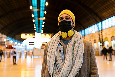 Man with face mask and headphones looking away while standing at station - p300m2251077 by Ezequiel Giménez