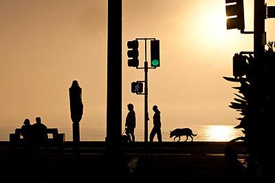 Silhouetted people walking along Redondo Beach in LA - p3314085 by Andrea Alborno