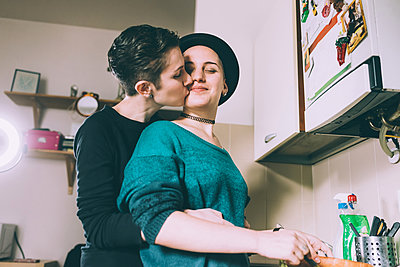Young woman kissing girlfriend in kitchen - p429m1206896 by Eugenio Marongiu