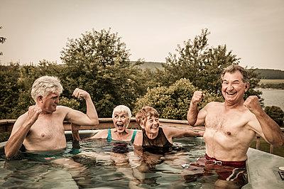 Older Caucasian couples relaxing in swimming pool - p555m1454175 by Jon Feingersh