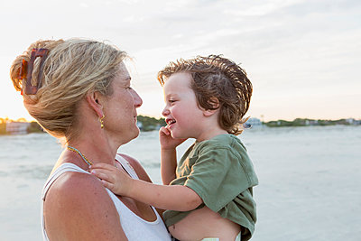 Caucasian mother holding boy at beach - p555m1522750 by Marc Romanelli