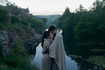 Caucasian couple wrapped in blanket hugging near river - p555m1532357 by Dmitriy Bilous