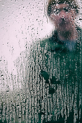 Man looking through rain splattered window - p597m2063524 by Tim Robinson