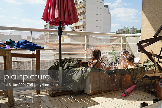 Children playing in a self made swimming pool on their balcony - p1610m2221795 by myriam tirler