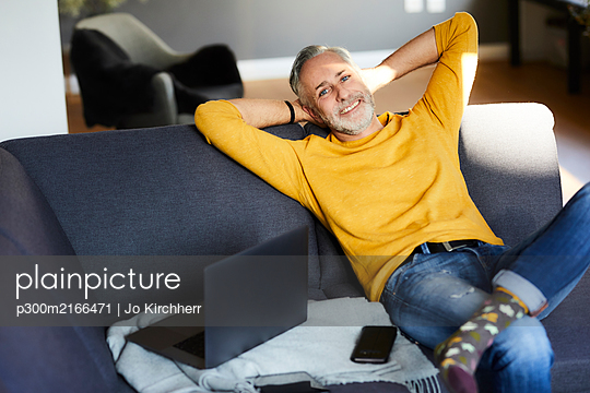 Portrait of smiling mature man relaxing at home - p300m2166471 by Jo Kirchherr