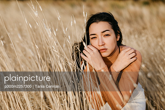 Serious young woman sitting amidst grass in field during sunset - p300m2257300 by Tania Cervián