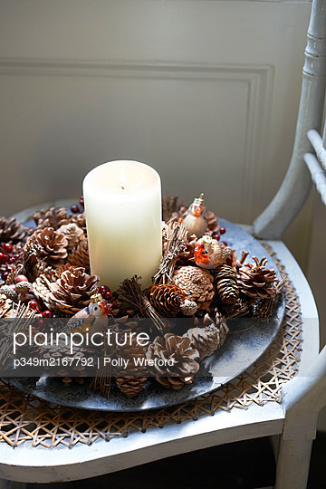Candle and pine cones on wicker chair seat - p349m2167792 by Polly Wreford