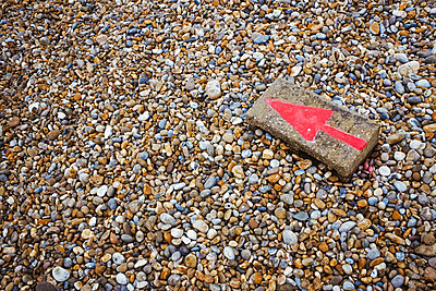 High angle view of red arrow painted on stone lying on pebble beach. - p1100m1490129 by Mint Images