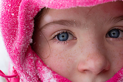 A close up of a girl Dressed for Winter with snowflakes in her eyelashes - p1166m2279580 by Cavan Images