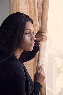 Beautiful Young Woman Looks out Window - p1617m2223541 by Barb McKinney