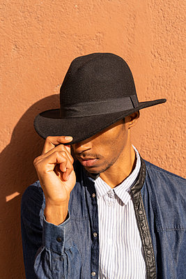 Stylish young man wearing a hat at a wall - p300m2155175 by VITTA GALLERY