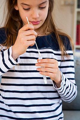 Girl putting nasal swab sample in test tube at home - p300m2282304 by Larissa Veronesi