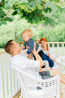 Parents with baby boy resting on balcony - p312m2049993 by Alicia Swedenborg
