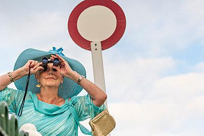 Senior woman at races looking through binoculars - p429m895361f by Colin Hawkins