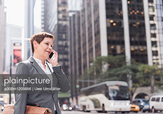 USA, New York City, businesswoman in Manhattan talking on cell phone - p300m1205666 by Uwe Umstätter