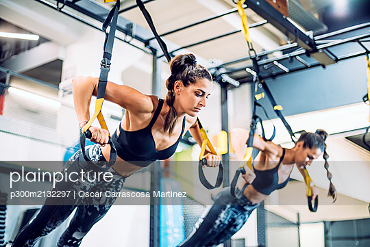 Twin sisters doing suspension traning in the gym - p300m2132297 by Oscar Carrascosa Martinez