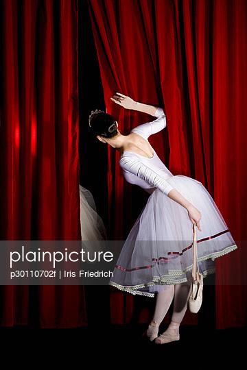 A ballet dancer peeking through a stage curtain holding a pointe shoe, rear view