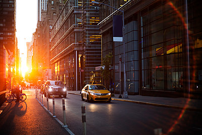 Vehicles on street amidst modern buildings during sunset - p1166m1163750 by Cavan Images