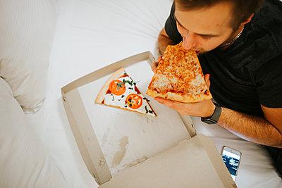Mann isst eine Pizza im Bett - p1507m2196518 von Emma Grann