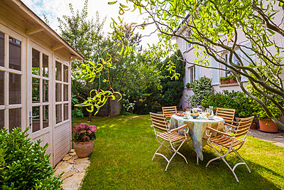 Garden shed and laid table in garden - p300m1166480 by Werner Dieterich