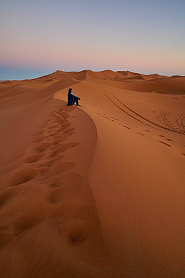 Morocco, woman sitting on desert dune at twilight - p300m2069503 by Maria Elena Pueyo Ruiz