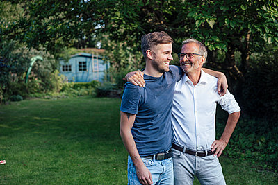 Father and son with arms around standing in backyard - p300m2277204 by Gustafsson