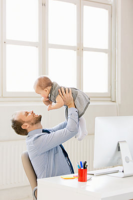 Father with baby girl in office - p312m1063614f by Susanne Kronholm