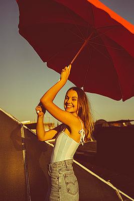 Junge Frau steht gut gelaunt auf Hausdach - p432m2217724 von mia takahara