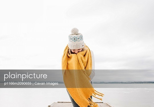 woman wrapped up in scarf smiling keeping warm at the beach - p1166m2090659 by Cavan Images