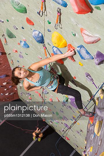 Mother belaying daughter climbing rock wall - p555m1312138 by Don Mason