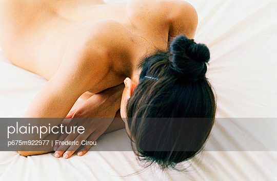 Nude woman lying face down on bed