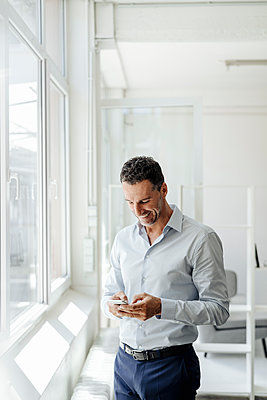 Smiling businessman in office at the window looking at cell phone - p300m1499533 by Kniel Synnatzschke