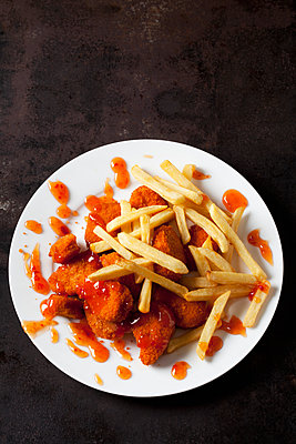 Plate of Chicken Nuggets with sweet chili sauce and French Fries on dark metal - p300m1567767 by Dieter Heinemann