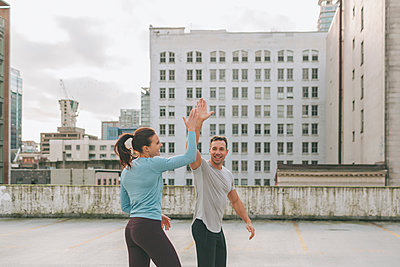 Man and woman high five during a workout in the city, Vancouver, Canada - p300m2169964 by Crystal Sing