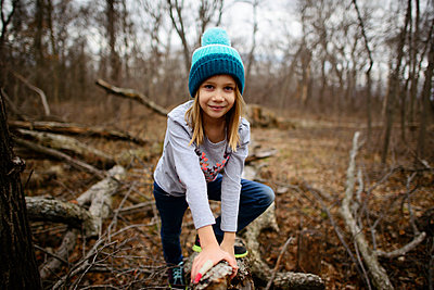 Portrait of confident girl leaning on dried branch at forest - p1166m1486218 by Cavan Images