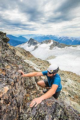 Climber wearing helmet scrambles up toward the summit of a mountain. - p1166m2162479 by Cavan Images