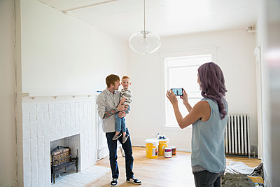 Mother photographing father holding son in empty new house - p1192m1158278 by Hero Images