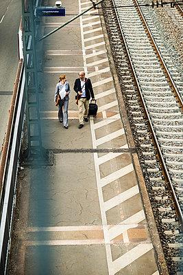Businessman and businesswoman walking on railway platform - p300m1028737f by Uwe Umstätter