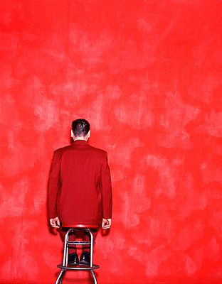 Man sits on stool facing red background - p3720535 by Erika Dufour