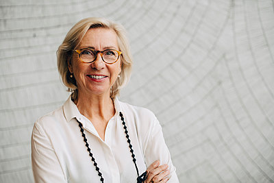 Portrait of smiling senior businesswoman standing against wall in office - p426m1588559 by Maskot
