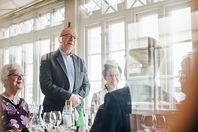 Senior friends talking seen through glass in restaurant - p426m2149134 by Maskot
