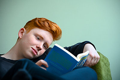 Red-haired girl reading a book - p427m2152768 by Ralf Mohr