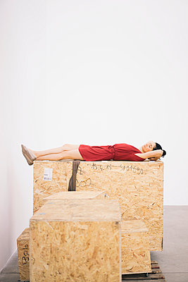 Woman in red dress on wooden box - p586m1034878 by Kniel Synnatzschke