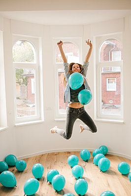 Young woman in new apartment playing with balloons - p586m1064897 by Kniel Synnatzschke