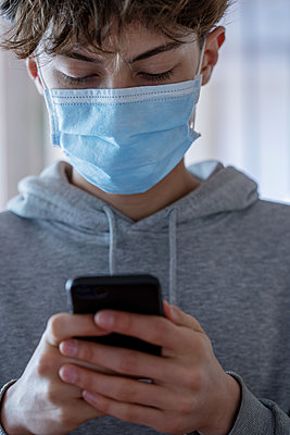Close up of teenage boy with medical mask using smartphone during coronavirus - p623m2186371 by Frederic Cirou