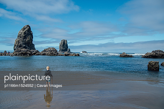 Rear view of boy walking on shore at beach against sky - p1166m1524552 by Cavan Images