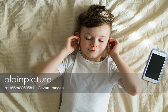 boy listening music with headphones on bed - p1166m2269581 by Cavan Images